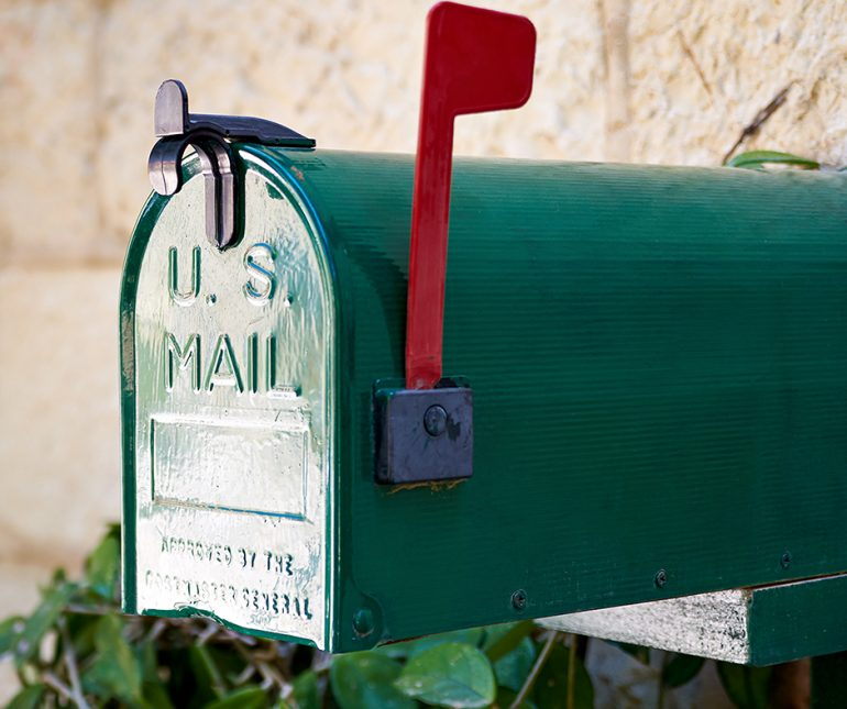 Green US Mail box with red flag up